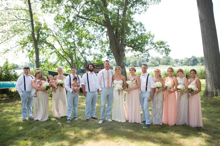 Khrysty and Dylan's choice of soft pinks, blues, and greens was inspired by the natural lakefront setting and July weather. The groomsmen wore light peach rose boutonnieres, which popped against the navy suspenders and white shirts. The bridesmaids mixed-and-matched in long off-white to pale peach dresses.
