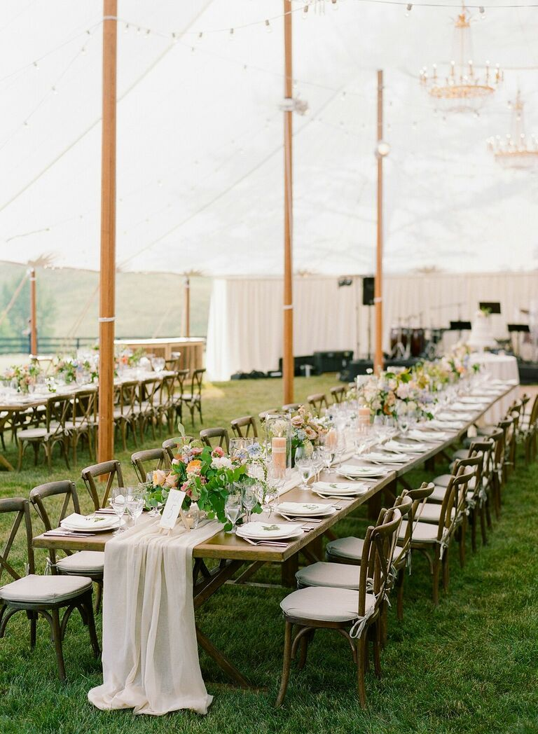 Rustic tented reception with farm tables