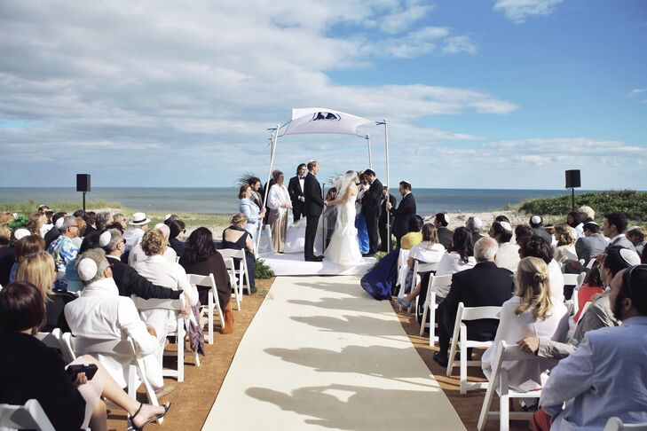 The ceremony took place with views of the Atlantic Ocean. A beige carpeting was used to appear like sand and a sisal runner lined the aisle. The huppah was created from a quilt border sewn by Will's mother.