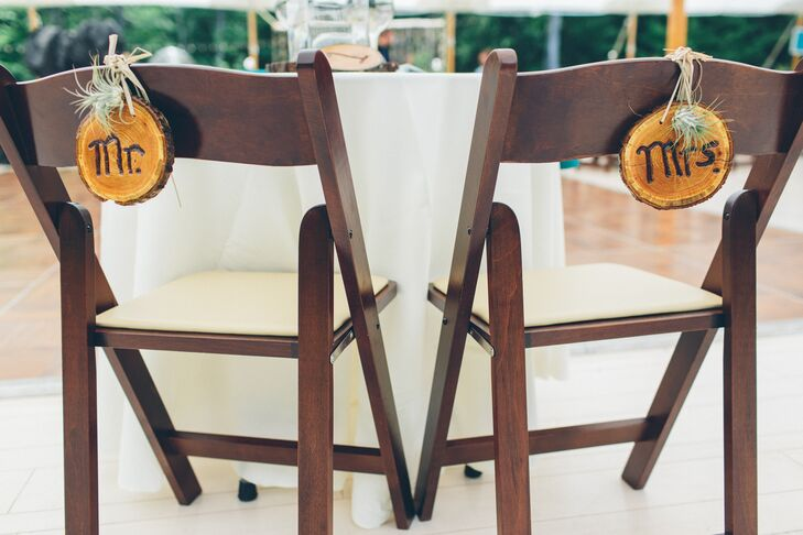 Wood slice signs that said Mr. and Mrs. hung off the back of the brown folding chairs.
