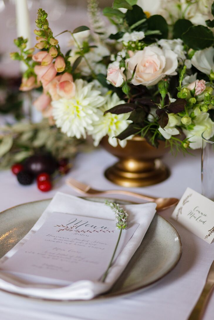 Garlands of lush greenery and abundant bouquets of dahlias, roses and foxgloves enlivened the elegant tablescape, while a fresh sprig of lavender at each place setting and stoneware dishes amplified the country charm.