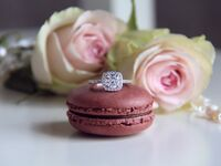 Diamond engagement ring on top of pink macaron