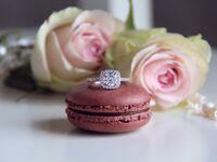 Diamond engagement ring on top of pink macaron