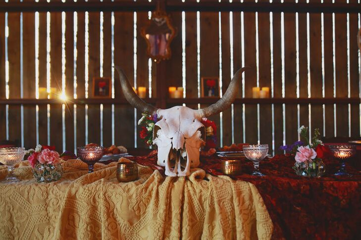 For the reception, Pretty Lovely Events took Madelyn's vision for a romantic, bohemian soiree to the next level, filling the rustic Riverwood Barn and Amphitheater in Durant, Oklahoma, with a palette of rich red, pink and purple and original details that provided endless visual intrigue and a one-of-a-kind aesthetic. Tables were draped in swaths of textured red and gold fabric and dotted with colored glassware, bud vases bearing bright pink blooms and quirky elements like cow skulls and antlers that knocked the day's theme out of the park.