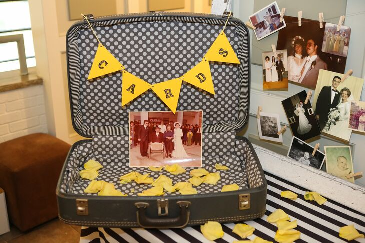 A vintage suitcase, surrounded by old family photos, was a lovely place for guests to leave cards for the newlyweds.