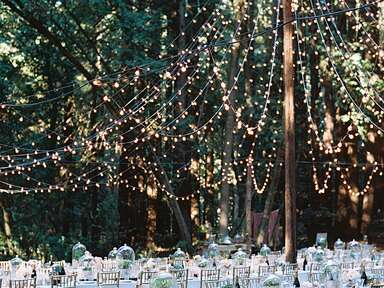 Outdoor wedding reception with tent-shaped string lights
