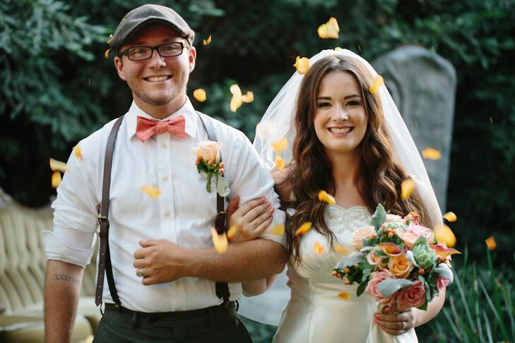 Katie and Dustyn walked up the aisle after their ceremony, showered by orange petals thrown their way in celebration of their marriage. Dustyn had a single orange rose mixed with hypericum berries pinned to his white collared dress shirt, while Katie matched him with an orange and pink rose bouquet.