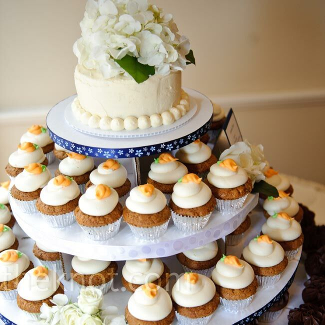 A cupcake tower of chocolate, carrot cake and white chocolate raspberry cupcakes was topped with a petite cutting cake adorned with hydrangeas.