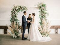 Bride and groom exchanging vows in front of lush floral arch and pampas grass