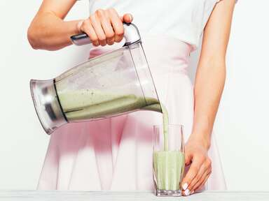 woman pouring smoothie out of blender