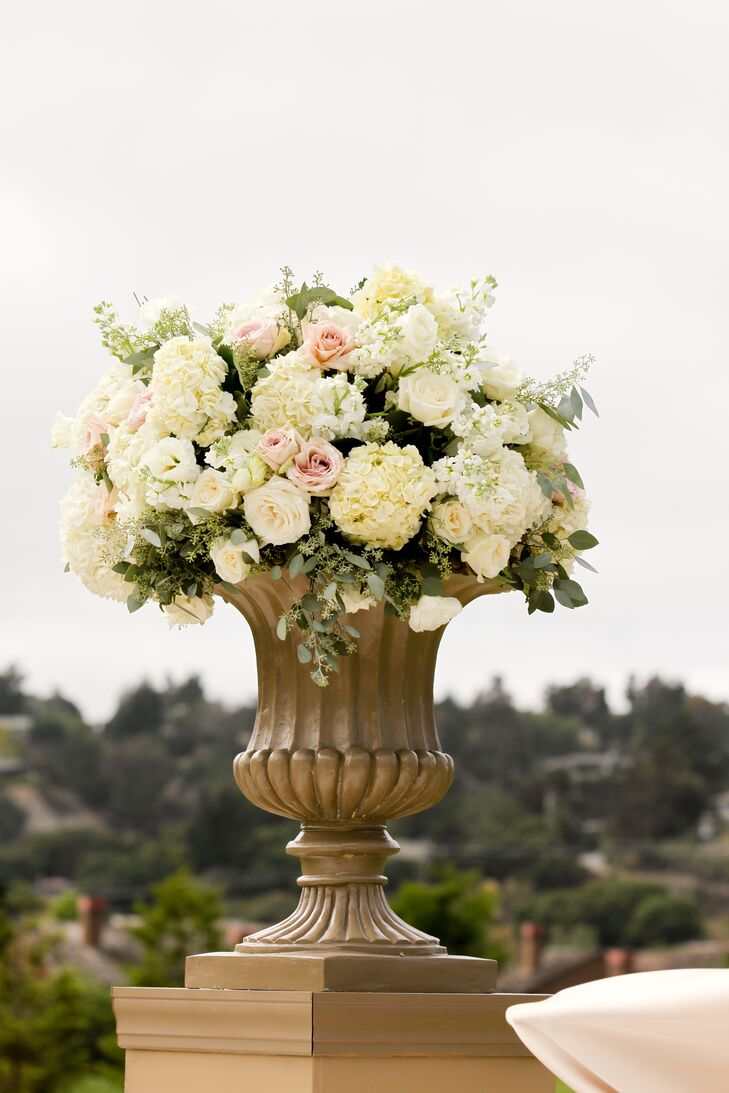 Soft ivory and blush floral arrangements of hydrangeas and roses gave the outdoor ceremony a romantic atmosphere.
