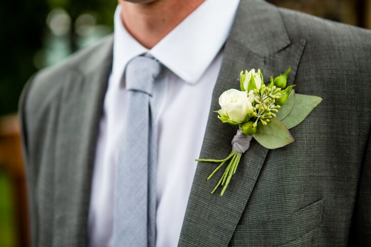 Jeff rocked a white rose, eucalyptus and leaf boutonniere, pinned to the lapel of his gray suit. The boutonniere matched Michelle's beautiful bouquet, filled with white garden roses and spray roses speckled with peach  blooms.