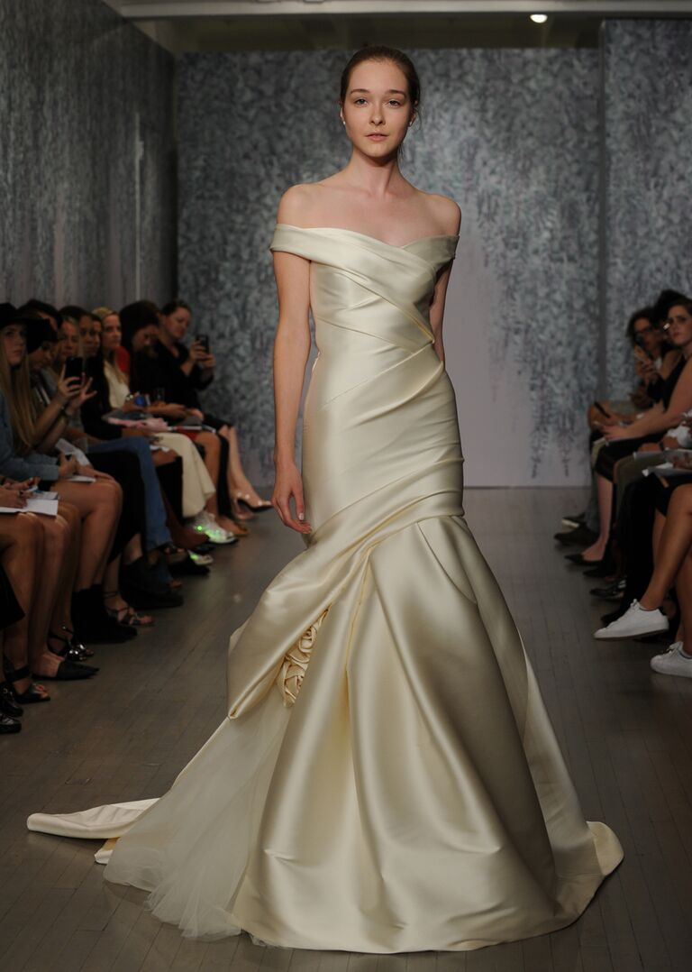 Monique Lhuillier wedding dress Fall 2016 Buttercup stretch Satin off-shoulder draped modified trumpet gown with hand tufted skirt and rosette accents