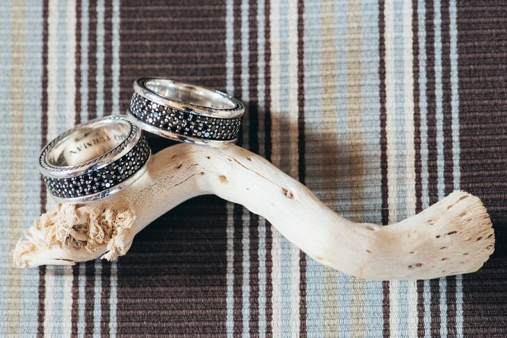 Both Cory and Randy picked out platinum rings with dark pave diamonds lining the center of the band, pictured here with an antler on a stripped background.