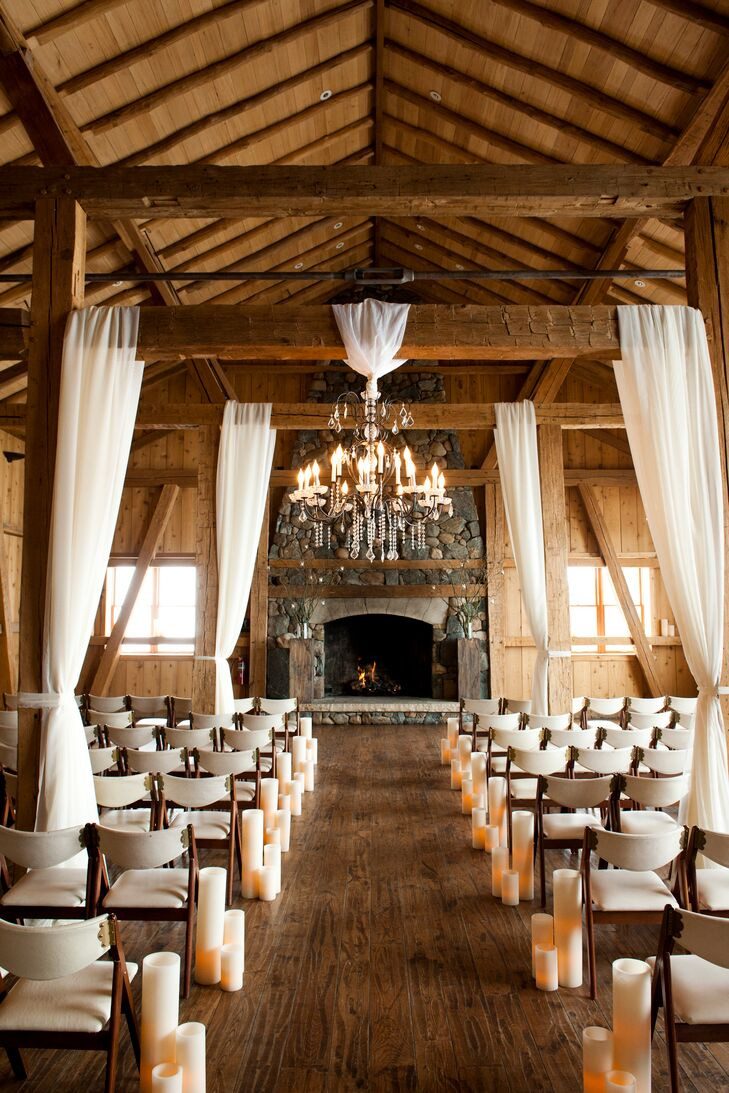 Panels of sheer, cream-colored fabric and elegant chandeliers were draped from the exposed wooden beams at Devil's Thumb Ranch to give the rustic space an elegant, romantic touch.