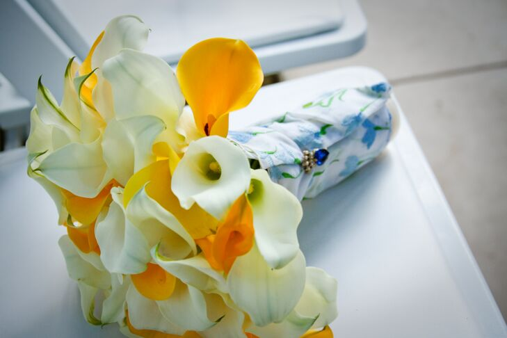 The bridal bouquet was a canary yellow and ivory assortment of calla lilies. A white wrap adorned with a blue floral design wrapped around the stems of the bouquet and was clipped with a sapphire stone.