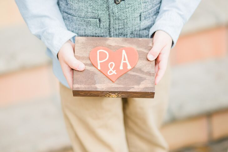 The ring bearer carried a wooden box down the aisle that Alison stained herself. As a personal touch, she added her and Pierce's initials onto an orange heart to tie into their wedding colors.