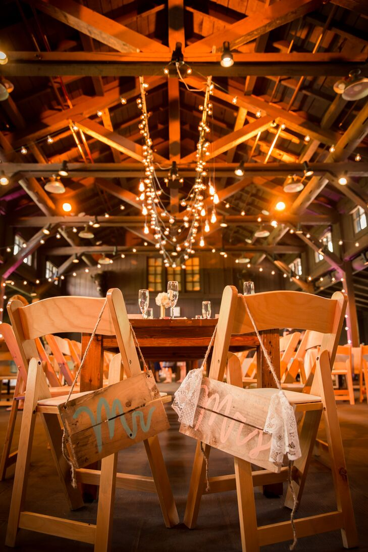 """Keeping with the blue and coral color palette, """"Mr."""" and """"Mrs."""" were painted in these colors on wooden signs and hung from Samantha and Ben's dinner chairs."""