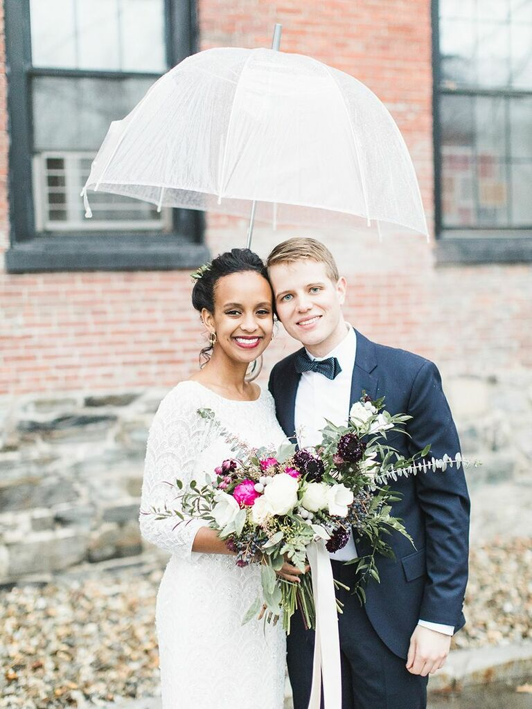 bride and groom under umbrella holding wild bouquet