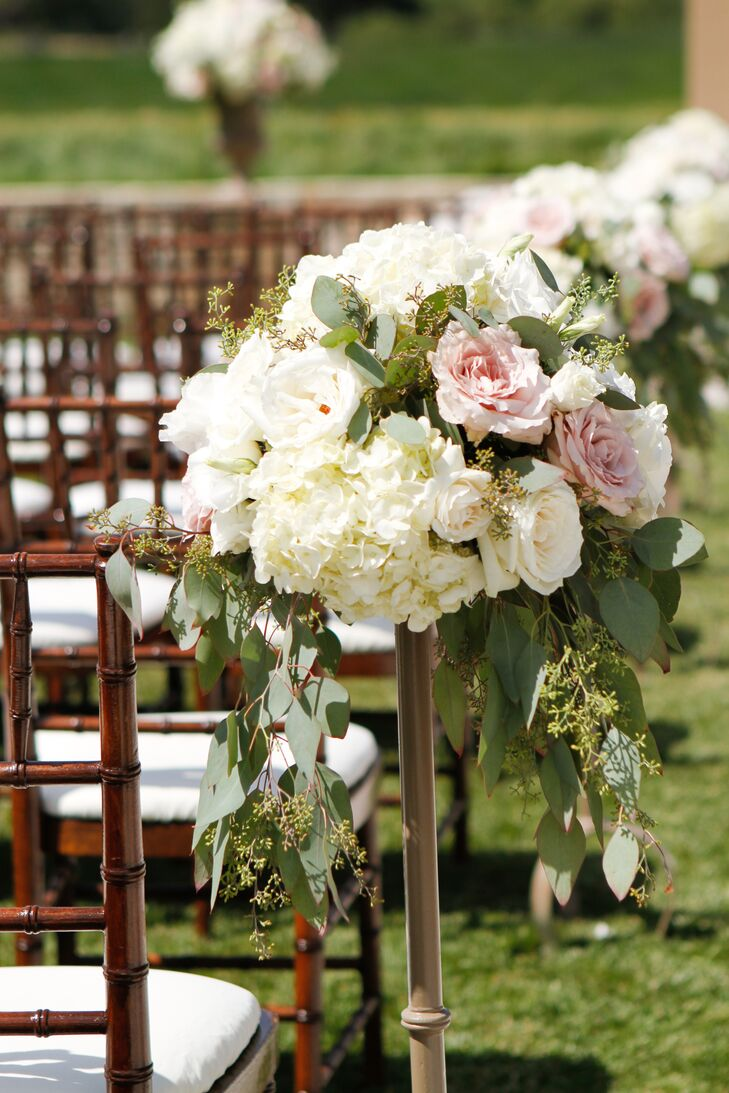 Seeded eucalyptus, roses and hydrangeas made up the blooming aisle markers at the ceremony.