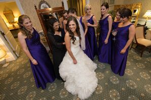 Bride Shares a Candid Photo with her Bridesmaids in Maxi Length Purple Dresses