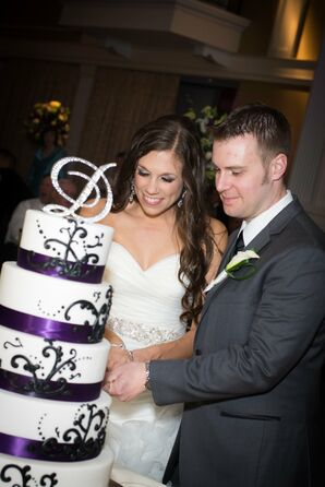 Bride and Groom Cut Their Elegant White Cake with Purple Trim