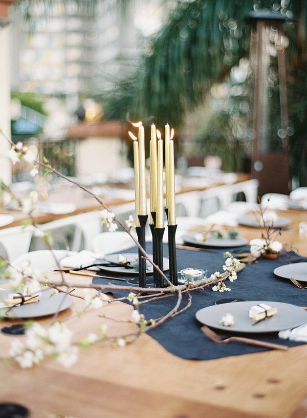 Gold taper candles in black candle holder