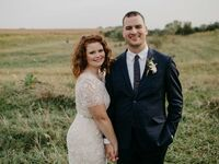 wedding couple poses with field backdrop
