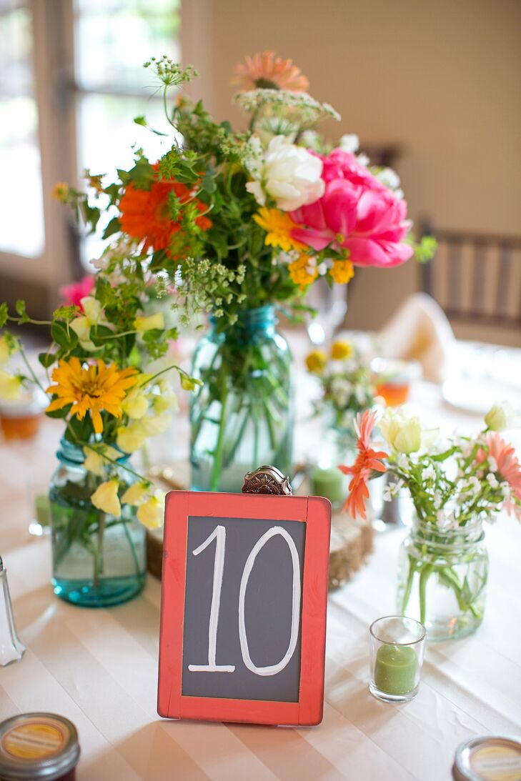 Loose arrangements of peonies, gerbera daisies and wildflowers filled antique Mason jars.