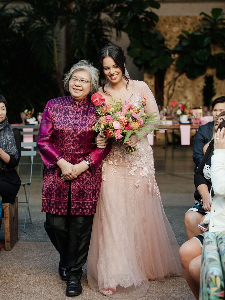 Bride walking down the aisle with mother at wedding ceremony