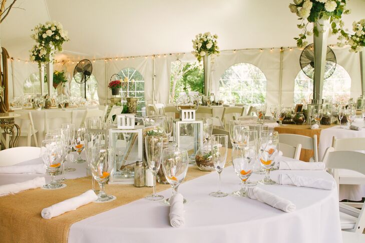 Tall floral centerpieces mixed with lanterns and burlap table runners.
