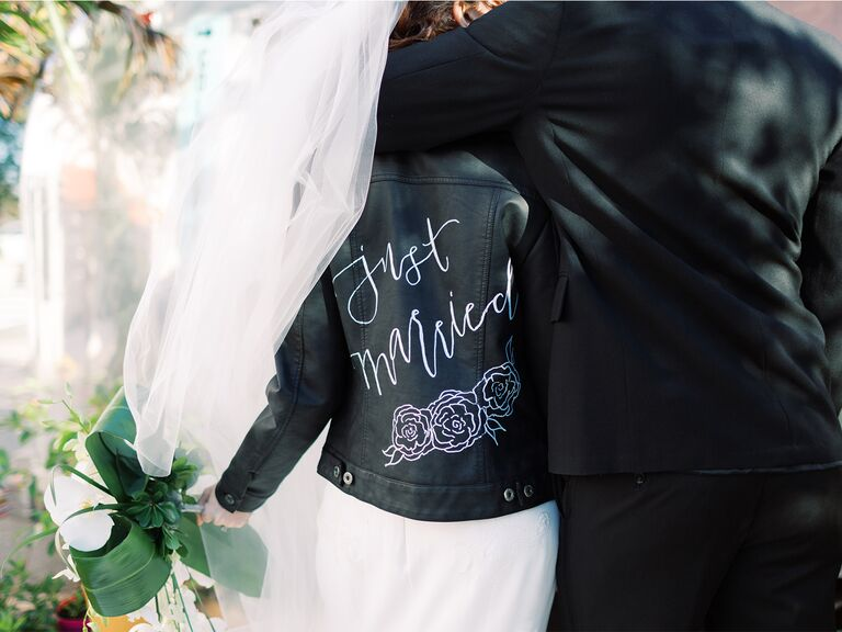 wedding couple bride wearing leather jacket with just married on the back