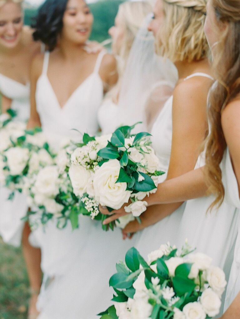 Bridesmaids in white dresses holding white wedding bouquets
