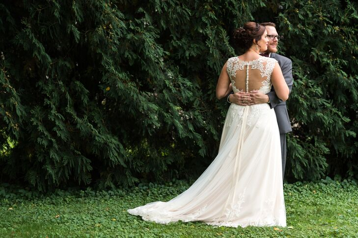 Sarah wanted the vintage feel of her wedding incorporated in her gown as well. She found an A-line, lace-over-matte side-satin gown with sparkling beading, an illusion back with covered buttons and cap sleeves. A grosgrain ribbon matching the cafe underlay of her dress accentuated her waist.