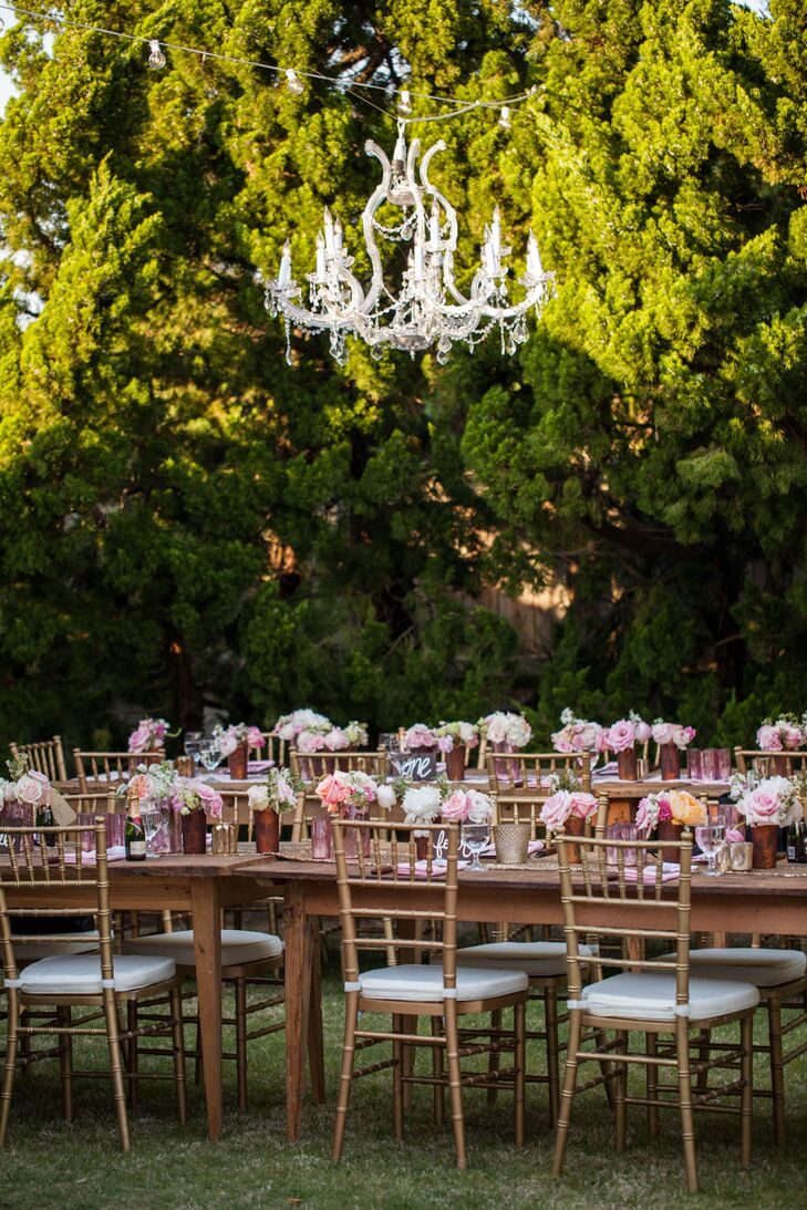 The reception took place on a perfectly manicured lawn next to the ocean in Corolla, North Carolina. Ryan and Brian, with the help of wedding planner Glam and Lace, decorated the space with wooden farm tables, sparkly gold runners, gold chiavari chairs, and pink and peach centerpieces.
