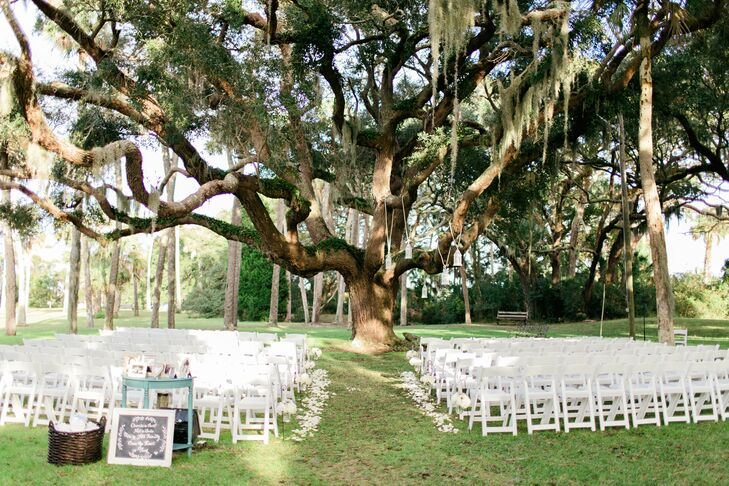 The couple married outside beneath a large oak tree. Rustic lanterns hung from the branches, while white rose petals and mason jars filled with succulents and mums lined the aisle.