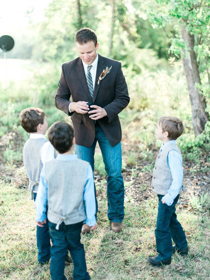 Brad takes a moment to explain to the boys how to greet guests as they walk into the ceremony and give each one a fresh flower. The flower boys were dressed in jeans and boots paired with a gray vest and blue tie over a white long-sleeve button-down.