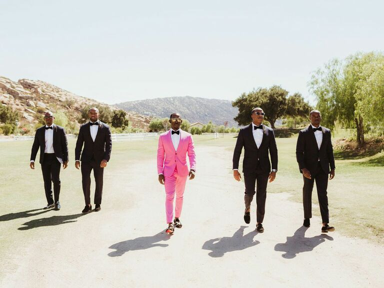 Groom and groomsmen walking outside scenic mountain wedding venue