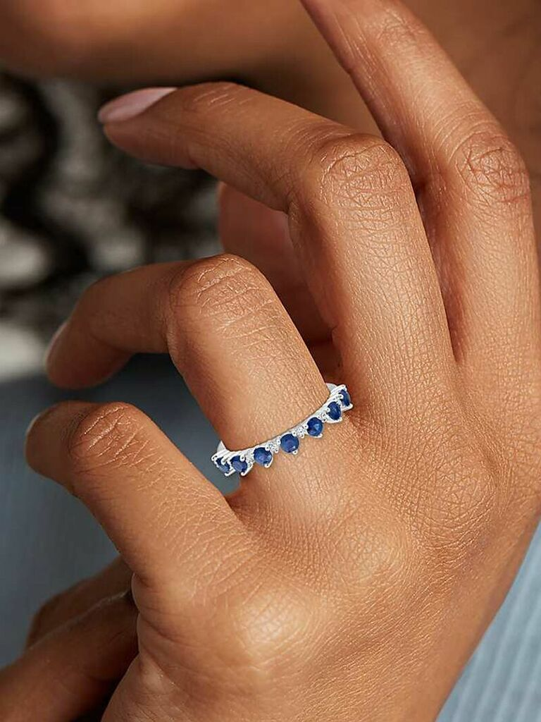 Close up of sapphire tiara stacking ring on woman's finger
