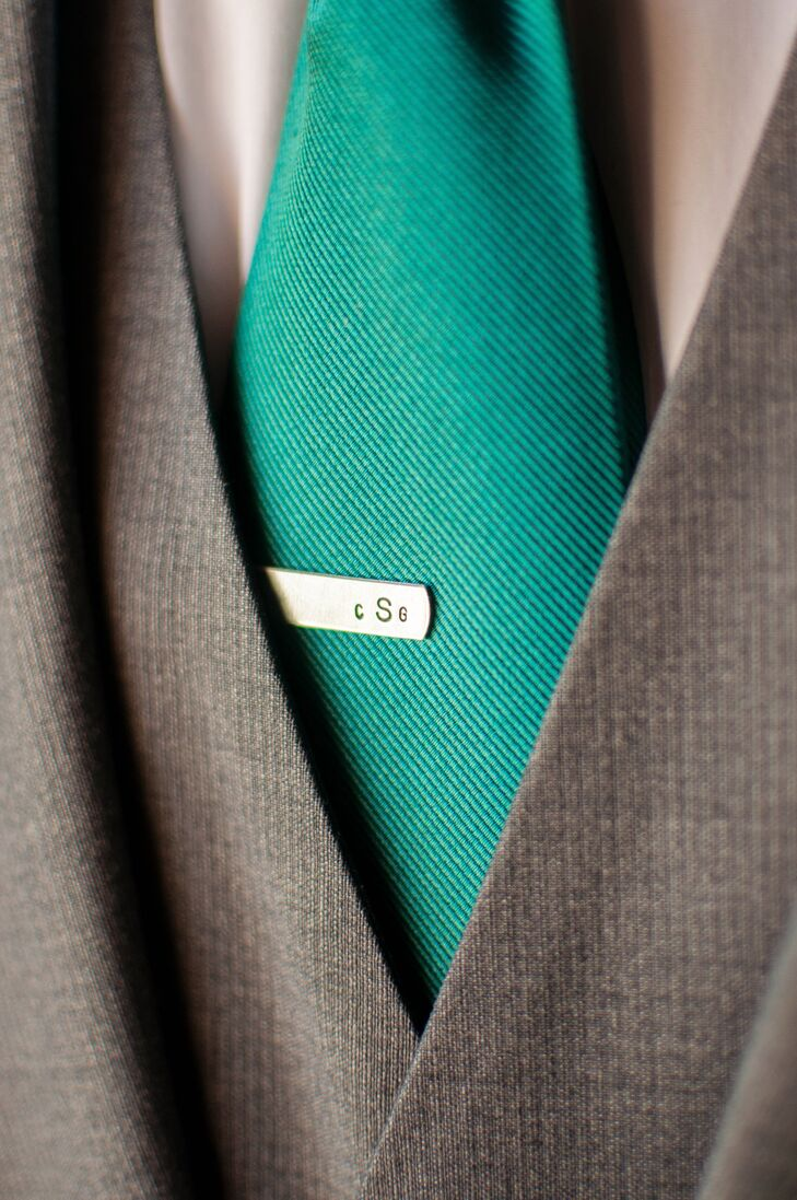 The groom accessorized his teal tie with an elegant monogrammed tie clip. While the groom wore a traditional jacket, his groomsmen stuck to shirts and suspenders.