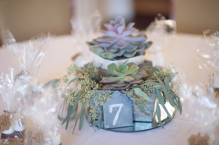 Abbey and Alex's centerpieces and flower arrangements were crafted by It's All in the Details. Succulents and seeded eucalyptus were placed in breakaway vases on each reception table.