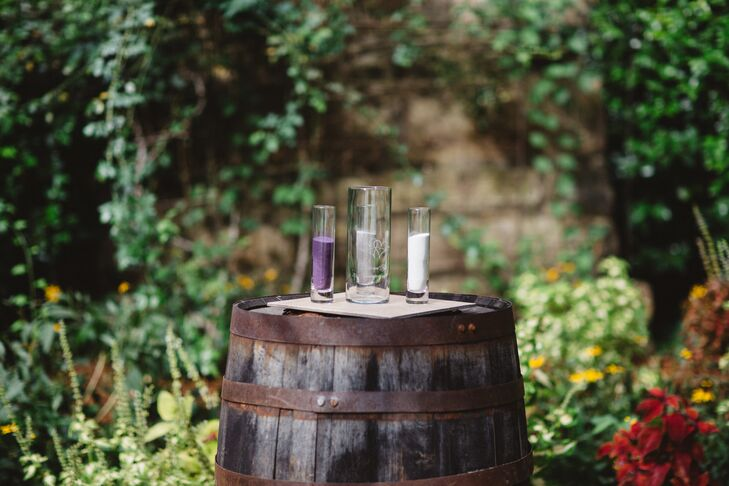 "A repurposed wine barrel sat under Katie and Kyle's wedding arbor and held two jars, one of purple and one of gray sand. ""We poured the sand into a vase to symbolize our union,"" Katie says."