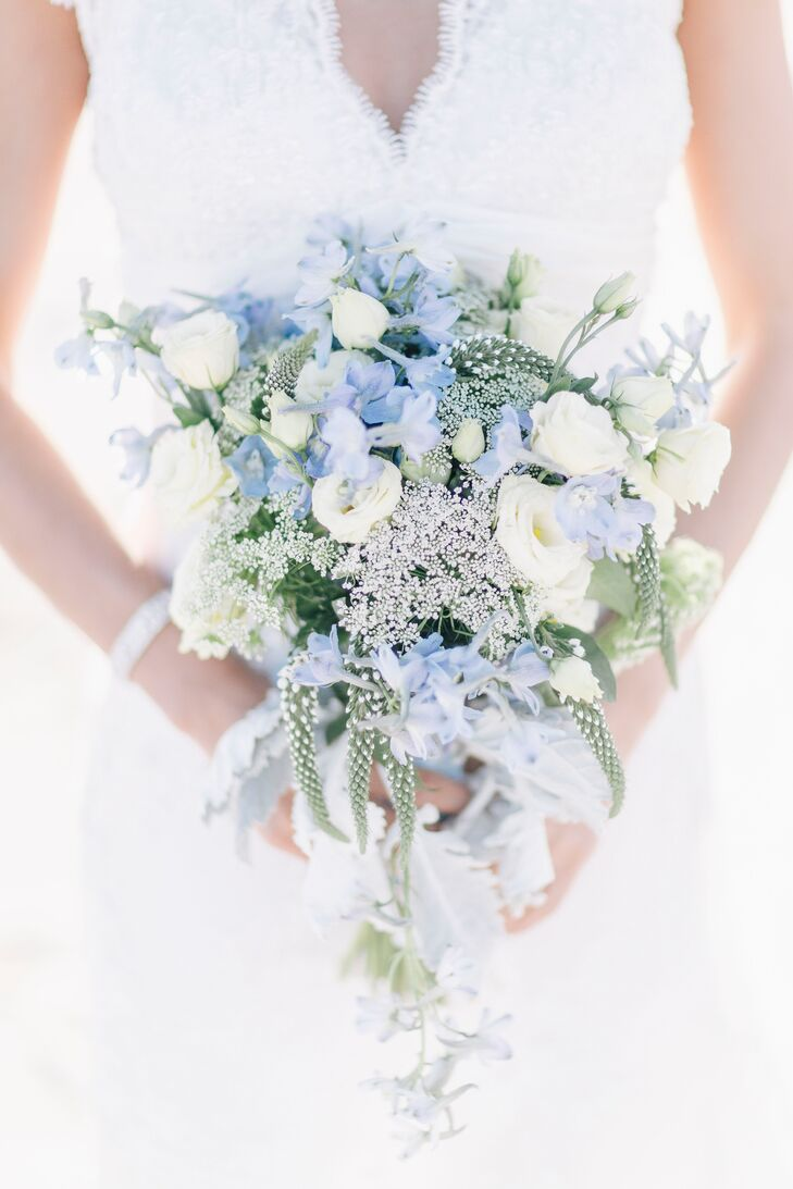 """Stephanie chose a bouquet of pale blue and yellow flowers, which fit perfectly with the whimsical beach vibe of their wedding. """"My mother said no white flowers because of superstition,"""" says Stephanie. The bouquets were tied with lace ribbon."""