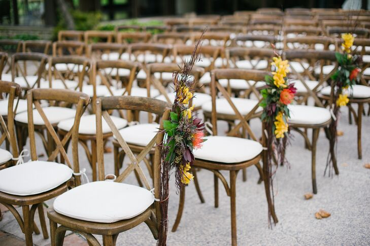 Wooden farm chairs and fall-inspired flower bunches complemented the natural surroundings of the outdoor ceremony space at Darby House in Galloway, Ohio.