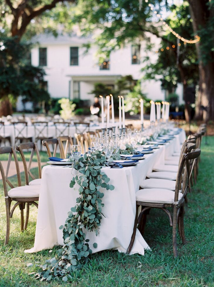 Laurie and Brian's head table was dripping with greenery! A lush garland of eucalyptus from Missy Gunnels Flowers cascaded past every place setting before it fell back onto the grass, matching the natural landscape at Southwood House and Cottages in Tallahassee, Florida.