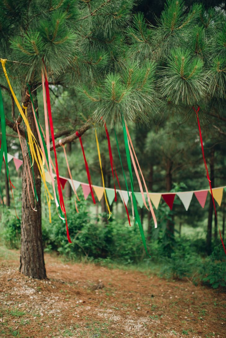 """Red, yellow and green ribbon streamers, pennant flags and paper hearts decorated the outdoor wedding space where Namia and Jared said """"I do."""""""