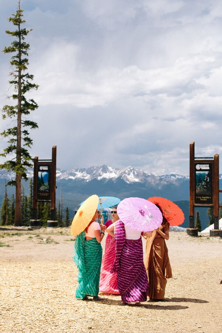 Guests in Colorful Indian Attire with Umbrellas on Mountaintop