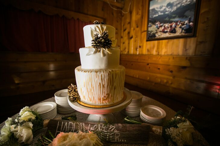 Shelby and Wyatt enjoyed a three-tier white fondant wedding cake decorated with gold on the bottom layer to look like a tree. The cake was topped with gold-covered pinecones to match the winter wedding theme.
