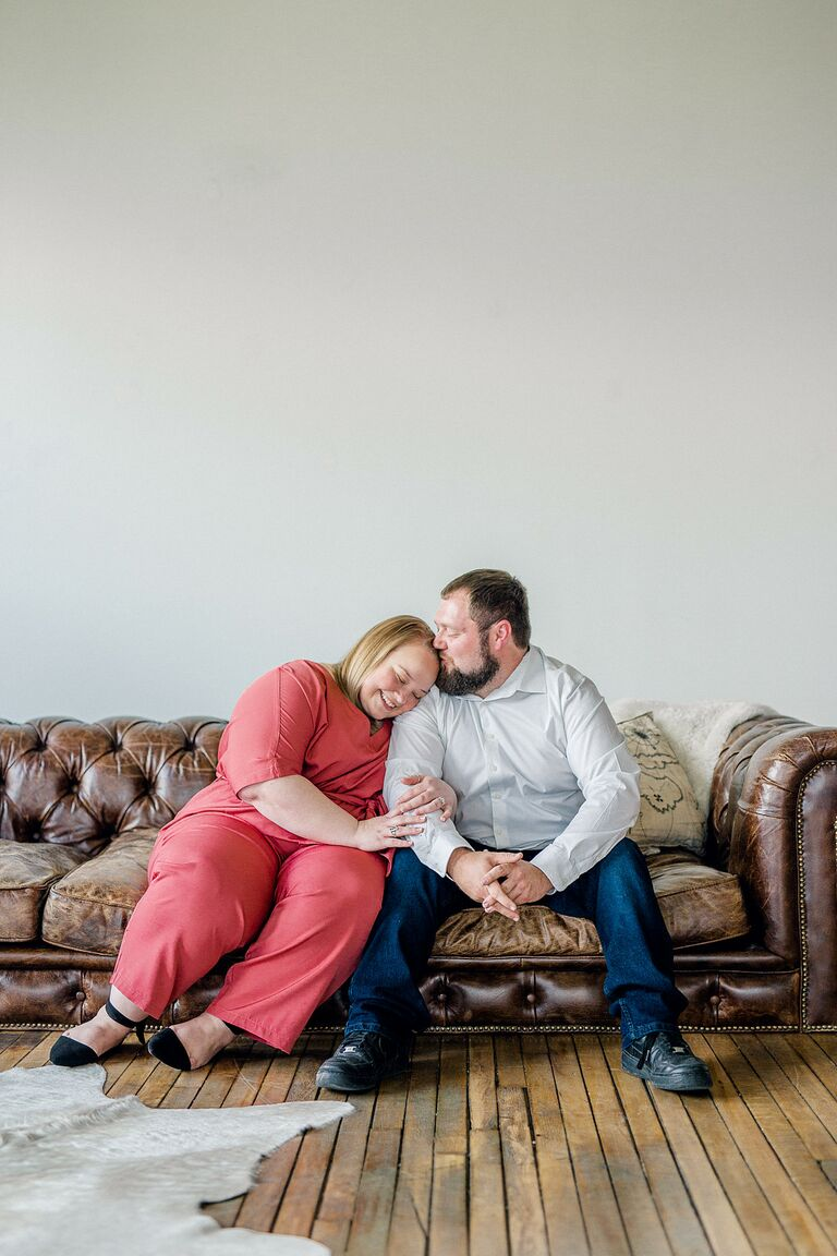 Couple cuddles on couch during engagement session