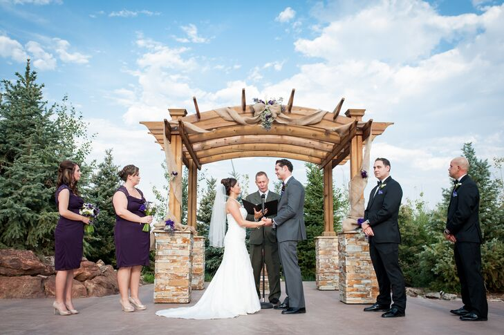 Tanya and Cody exchanged vows under a rustic rock-and-wood wedding arch decorated with burlap linens and purple and ivory flowers.